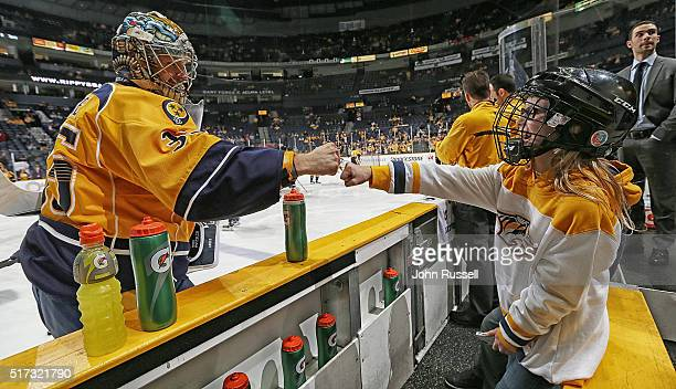 Pekka Rinne of the Nashville Predators fist bumps a young fan on the bench during warmups prior to an NHL game against the Vancouver Canucks at...