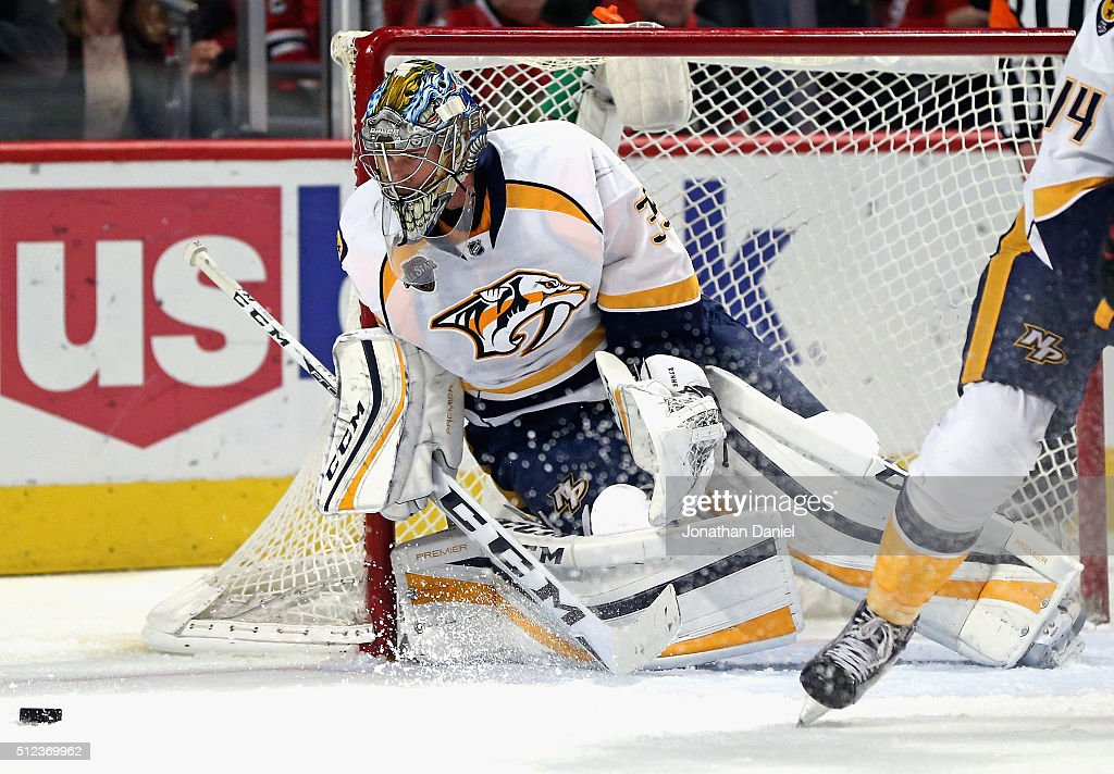 Pekka Rinne of the Nashville Predators knocks the puck away for a save against the Chicago Blackhawks at the United Center on February 25 2016 in...