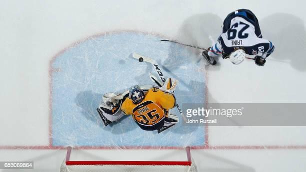 Pekka Rinne of the Nashville Predators makes an overtime save against Patrik Laine of the Winnipeg Jets during an NHL game at Bridgestone Arena on...