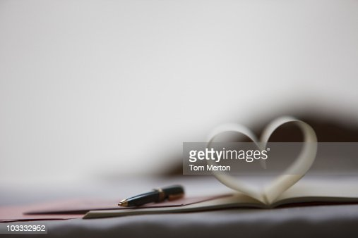 Pen and pages of notebook forming heart-shape : Stock Photo