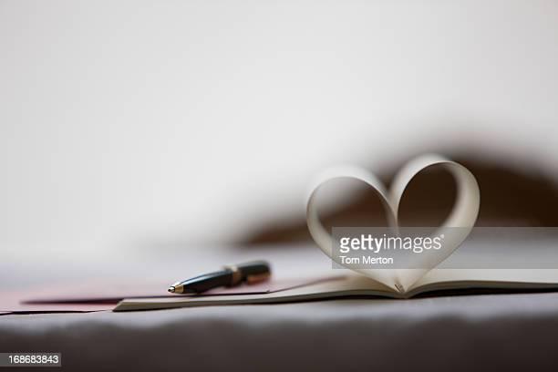 Le pagine di Blocco note e penna formando a forma di cuore