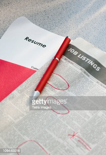 Pen on newspaper job listings with resume
