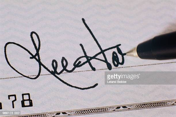 Pen writing signature on cheque, close-up