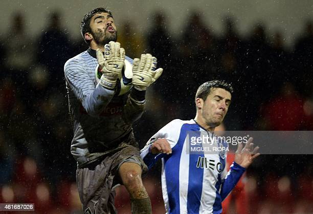 Penafiel's goalkeeper Tiago Rocha catches the ball beside Porto's Spanish defender Ivan Marcano during the Portuguese liga football match FC Penafiel...