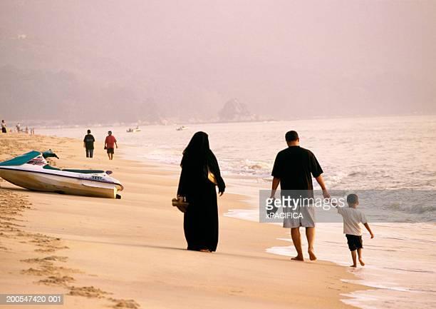 Penang, Malaysia. Arabic family walking past jet ski on beach