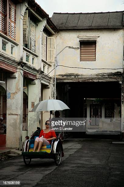 Penang rickshaw in the backstreets of George Town shuttling a passenger through the alleys The cycle rickshaw is a smallscale local means of...
