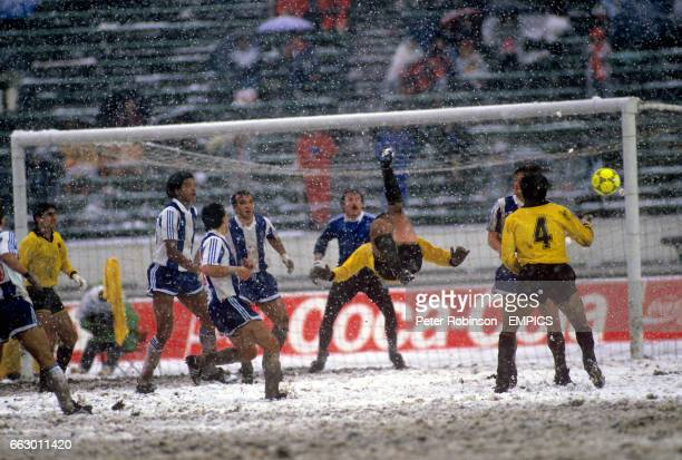 A Penarol player misses an over head kick as the players struggle in the extreme conditions