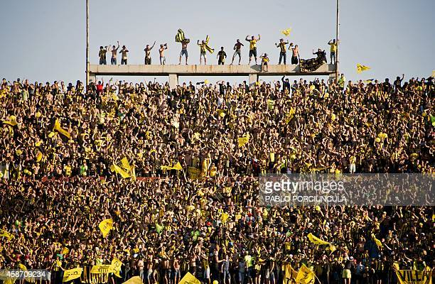 Penarol's supporters cheer their team after scoring a penalty against Nacional during the Uruguayan first division football derby match at the...