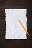 A pencil and a crumpled piece of paper flattened back out