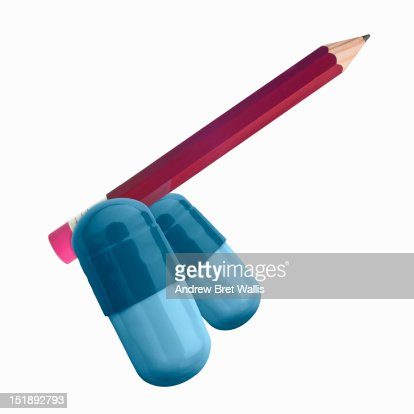 Pencil and pill capsules as male genitalia : Stock Photo