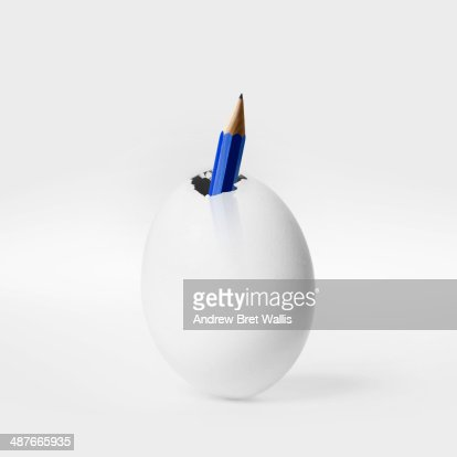 Pencil breaking out of an egg.