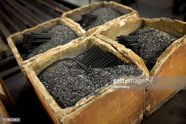 Pencil cores and a graphite mix sit in crucibles after being fired in a furnace at the General Pencil Co's factory in Jersey City New Jersey US on...