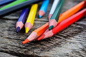 A close up image of colorful wooden pencil crayons on a wooden table.