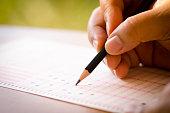 Close up pencil drawing selected choice on answer sheets