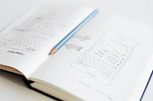 Pencil lying on an open diary with a sketch web design