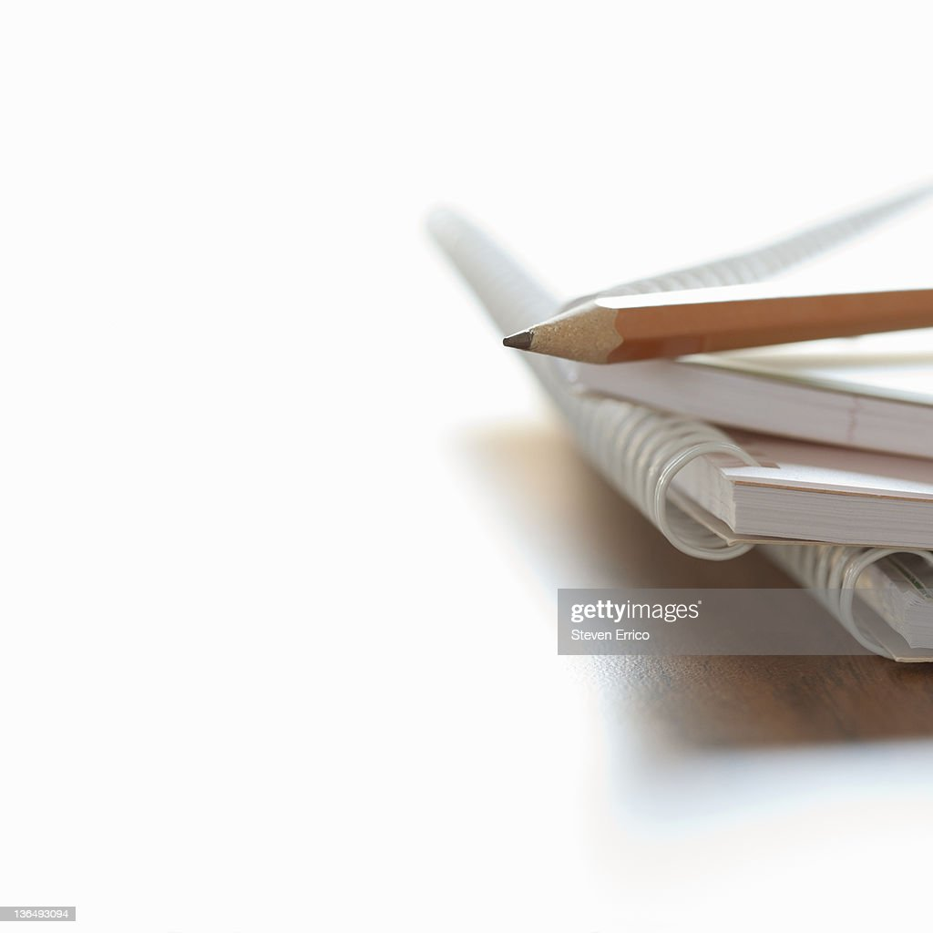 Pencil resting on blank spiral notebooks, close-up : Stock Photo