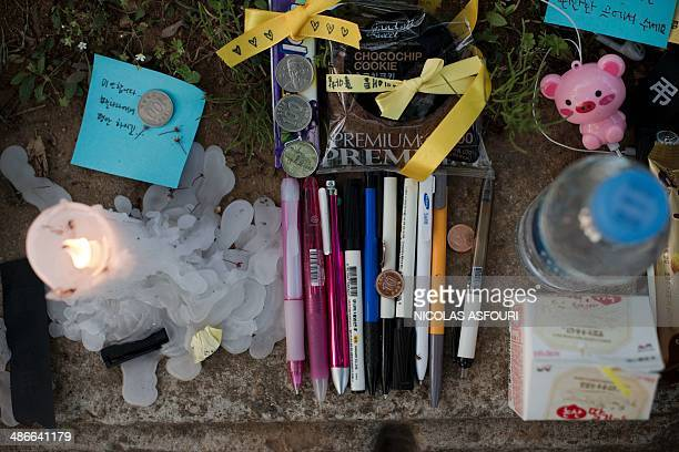 Pencils choco chips cookies a candle and messages are seen at a makeshift memorial at the main gate of Danwon High School in Ansan on April 25 2014...
