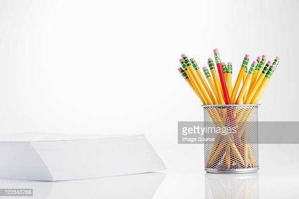 Pencils in pot and stack of paper