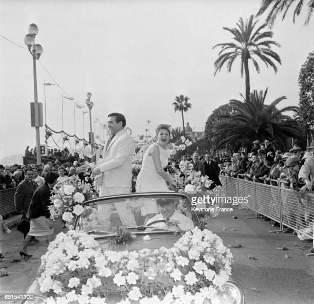 Pendant la Bataille de fleurs Louis Mariano et Annie Cordy lançant des fleurs d'une voiture sur la Promenade des Anglais à Nice France le 7 février...
