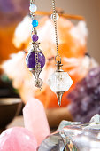 Pendulums crystal pendulum, amethyst, tool for dowsing. Crystals undrneath an in backbround.