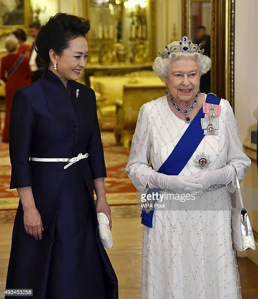 Peng Liyuan the wife of President of China Xi Jinping accompanies Britain's Queen Elizabeth II as they arrive for a state banquet at Buckingham...