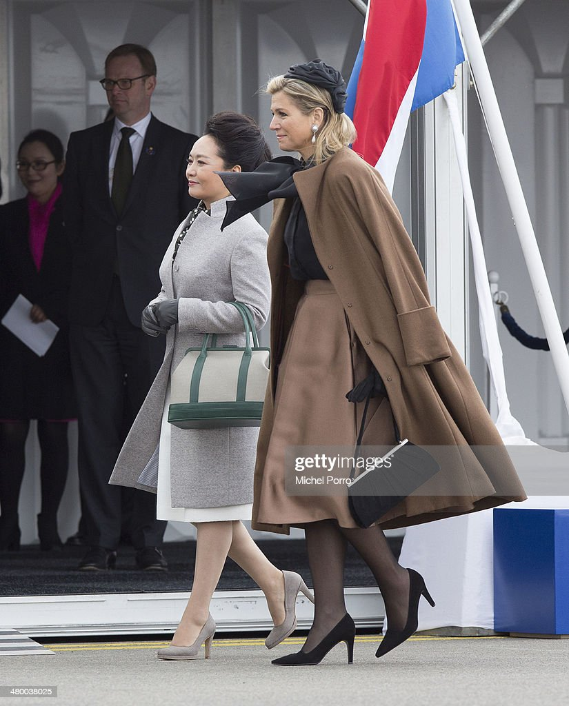 Peng Liyuan, wife of Chinese President Xi Jinping, (L) and Queen Maxima of The Netherlands attend the welcoming ceremony upon the arrival of Chinese President Xi Jinping at Schiphol International Airport on March 22, 2014 in Amsterdam, Netherlands. Xi Jinping is on a two-day state visit to the Netherlands ahead of the 2014 Nuclear Security Summit (NSS) in The Hague, which will be held on March 24-25.