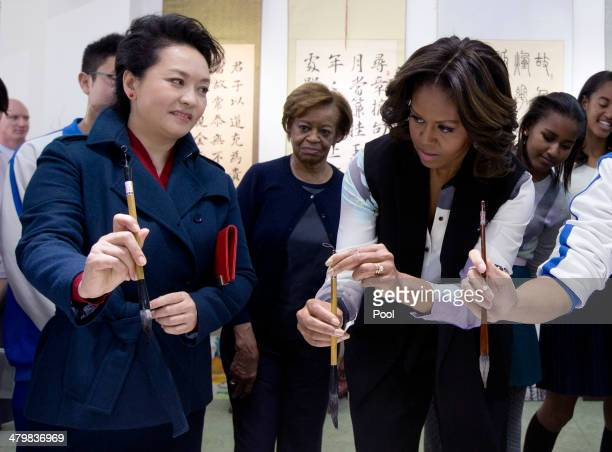 Peng Liyuan wife of Chinese President Xi Jinping left shows US first lady Michelle Obama how to hold the writing brush as they visit a Chinese...