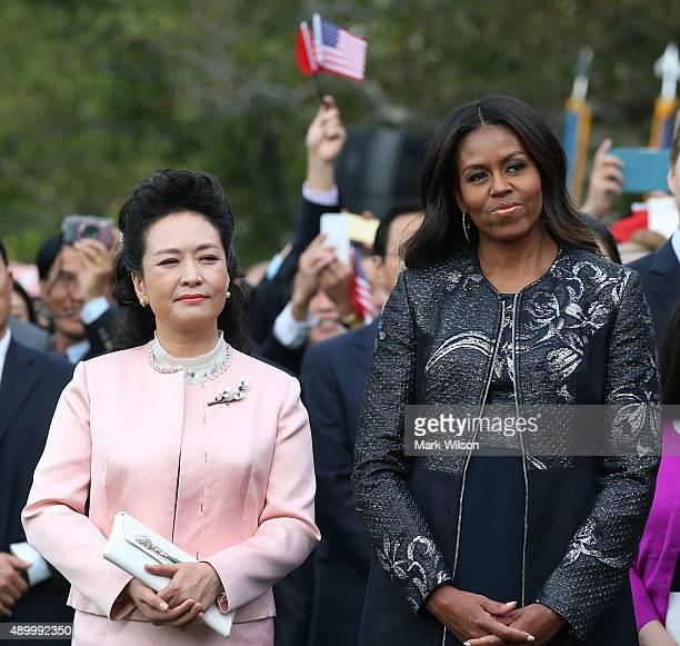 Peng Liyuan wife of Chinese President Xi Jinping stands with US first lady Michelle Obama during a state arrival ceremony on the south lawn of the...