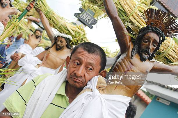 A penitent carries an image of Christ during The Procession of the Christs on March 24 2016 in Izalco El Salvador This procession is considered the...