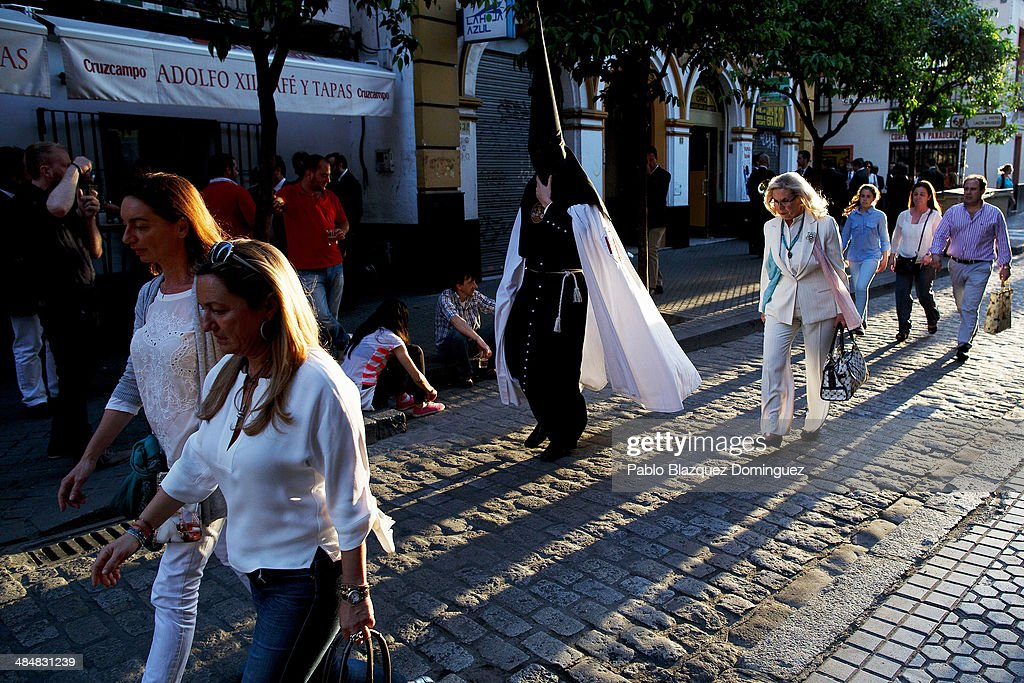 A penitent from 'El Museo' brotherhood walk next to people to the church to start a procession on April 14, 2014 in Seville, Spain. Easter week is traditionally celebrated with processions in most Spanish towns.