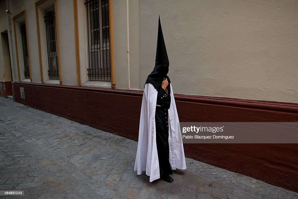 A penitent from 'El Museo' brotherhood walk to the church to start a procession on April 14, 2014 in Seville, Spain. Easter week is traditionally celebrated with processions in most Spanish towns.