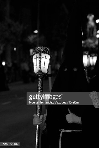 Penitent Holds Candles During Easter Holy Week