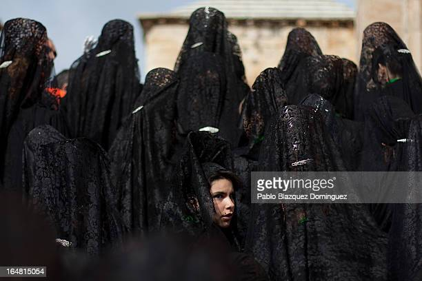 A penitent looks back as she and others wear mantillas ahead of the Holy Week procession of the Cofradia de la Virgen de la Esperanza on March 28...