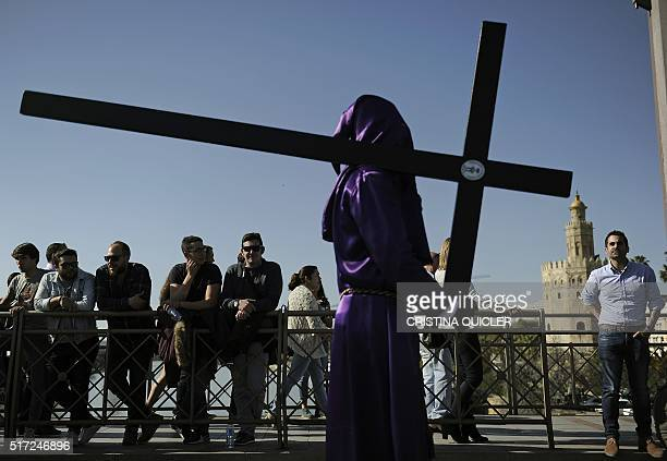 A penitent member of the 'Las Cigarreras' brotherhood carries a cross during the Easter procession in Sevilla on March 24 2016 Christian believers...