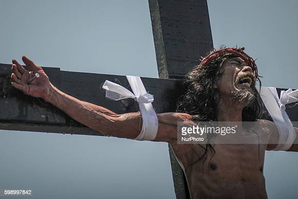 A penitent nailed to a wooden cross grimaces in pain as he takes part in a reenactment of Jesus Christ's crucifixion during Good Friday in San...