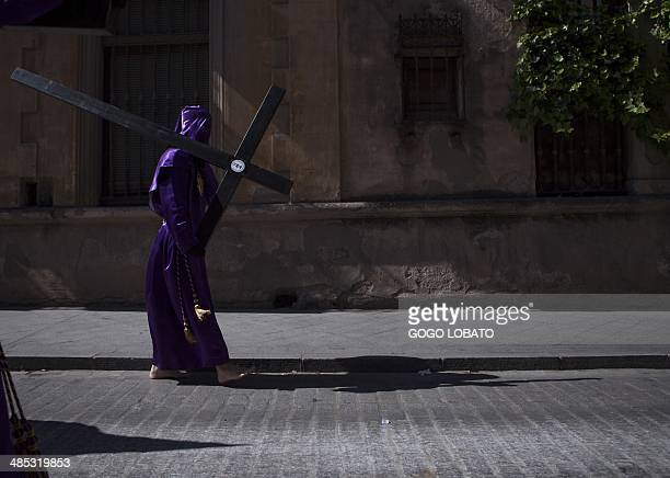 A penitent of 'Las Cigarreras' brotherhood carries a cross as he parades during a Holy Week procession in Sevilla on April 17 2014 Christian...
