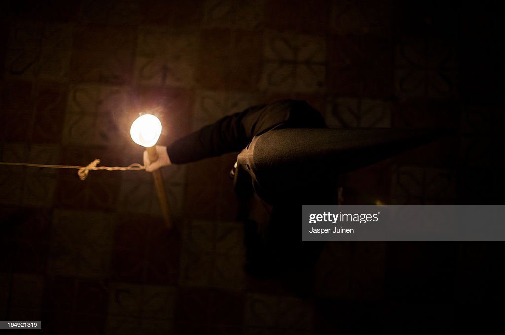 A penitent of the Cofradia del Santisimo Cristo del Silencio y la Expiracion brotherhood holds a candle while taking part in a holy week procession on March 29, 2013 in Luque near Cordoba, Spain. The origin of this small brotherhood, which uses a skull with crossed shins prominently as their symbol, referring to the mortality and short duration of life but also to the triumph of Jesus over death, dates back to the fifties when a group of young catholic's came up with the idea of forming the brotherhood. Since its founding the brotherhood has a strict penitential character with one of its aims being the public prayer of the Stations of the Cross in the early hours of Good Friday through the streets of this small Andalusian town. Home to the brotherhood is the San Nicolas de Tolentino convent church which was founded in 1626 and dedicated to Our Lady of Grace.