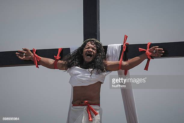 Penitent Ruben Enaje grimaces in pain as he hangs from a wooden cross while taking part in a reenactment of Jesus Christ's crucifixion during Good...
