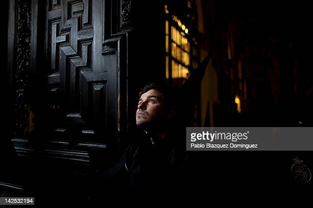 A penitent watches Nuestra Senora de Los Dolores figure of the Dolores brotherhood arrive at Cordoba's Mosque during the Holy Week procession on...