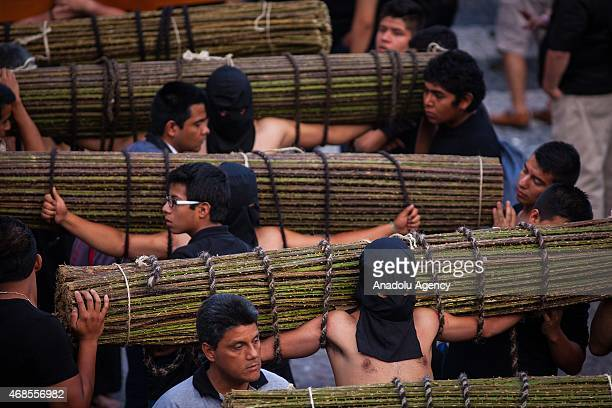 Penitents carry a rods bushes with thorns during the procession of Holy Friday in the city of Taxco Guerrero state Mexico on April 3 2015 The Holy...
