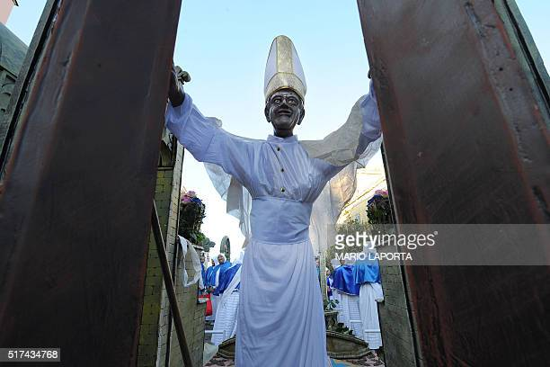 Penitents carry a wooden structure called 'Pope Francis Open Jubilee door' during a procession for Good Friday on March 25 2016 in the small island...