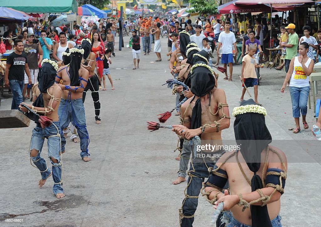 Penitents flagellate themselves as part of Lenten observance in Angeles City, Pampanga province, north of Manila on April 17, 2014. The dominant Roman Catholic church does not condone flagellation and other extreme acts of penitence including gory Good Friday reenactments of the crucifixion of Jesus Christ, but devout Catholics say it is a means of atoning for their sins and to implore God to spare them and other members of their families from illness or bad luck.