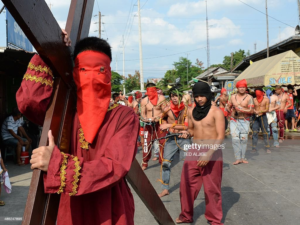 Penitents flagellate themselves while another carries a wooden cross as part of Lenten observance in Angeles City, Pampanga province, north of Manila on April 17, 2014. The dominant Roman Catholic church does not condone flagellation and other extreme acts of penitence including gory Good Friday reenactments of the crucifixion of Jesus Christ, but devout Catholics say it is a means of atoning for their sins and to implore God to spare them and other members of their families from illness or bad luck.