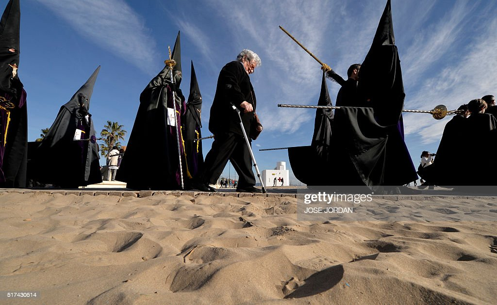 TOPSHOT Penitents from 'Cristo Salvador ' brotherhood walk along the sand during a Holy Week procession on March 25 at the beach in Valencia...