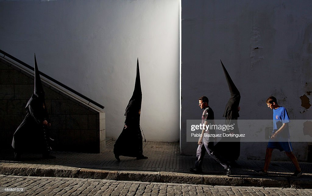 Penitents from 'El Museo' brotherhood walk to the church to start a procession on April 14, 2014 in Seville, Spain. Easter week is traditionally celebrated with processions in most Spanish towns.