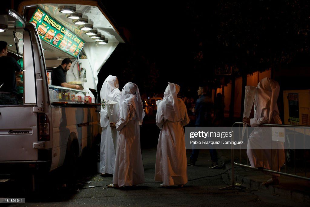 Penitents from 'San Gonzalo' brotherhood buy food at a mobile street food van after a 12 hour procession outside their church in the early hours on April 15, 2014 in Seville, Spain. Easter week is traditionally celebrated with processions in most Spanish towns.