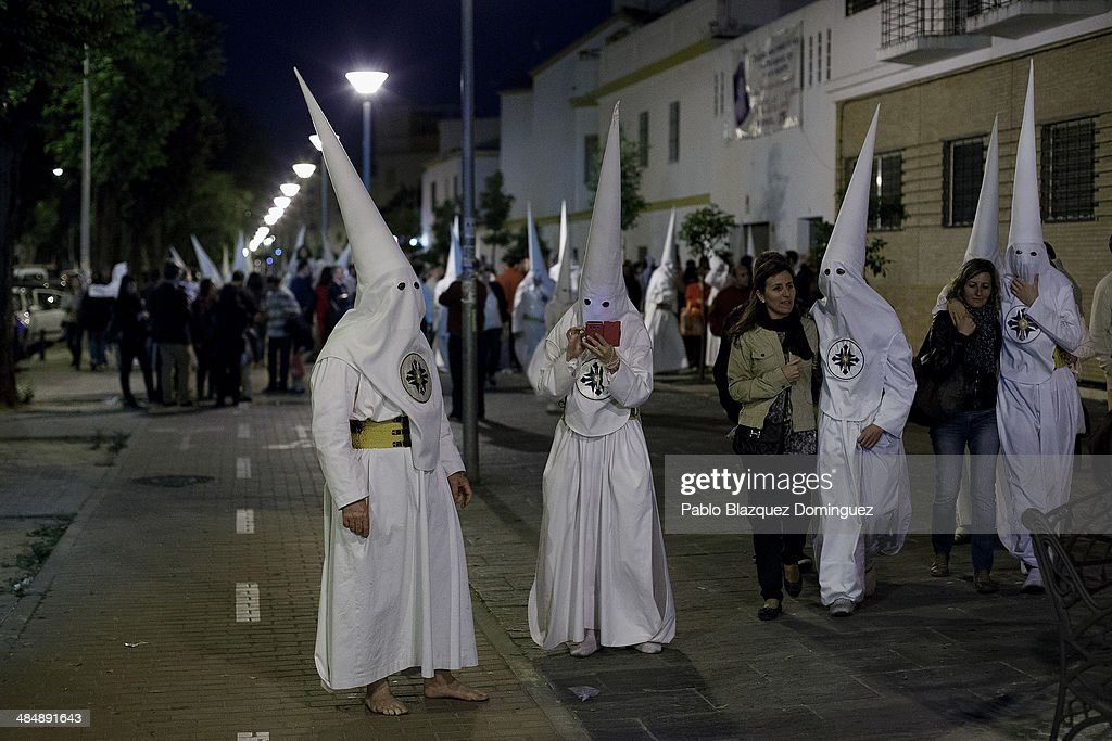 Penitents from 'San Gonzalo' brotherhood check their phones and meet their families after a 12 hour procession as they leave their church in the early hours on April 15, 2014 in Seville, Spain. Easter week is traditionally celebrated with processions in most Spanish towns.