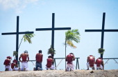 Penitents kneel before three crosses during penitensya as a form of penance during Good Friday on March 29 2013 in Pampanga Philippines Flagellation...