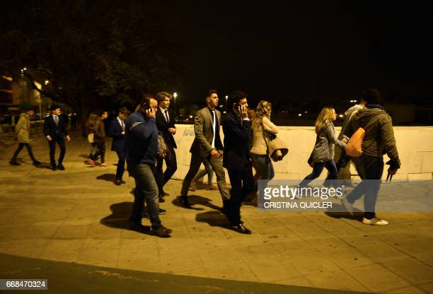 Penitents leave a Holy Week processional area following a stampede in Sevilla on April 14 2017 An outbreak of panic sparked by troublemakers caused...