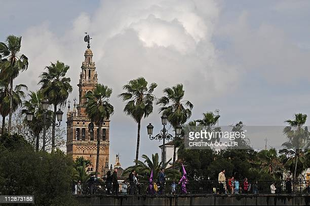 Penitents of 'La O' brotherhood procession walk to their church during the Holy Week in Sevilla on April 22 2011 Heavy rains forced church officials...